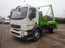 VOLVO FL skip loader truck by a